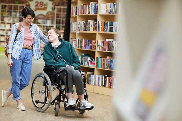 disabled-student-visiting-library-with-groupmate-P65DLWC400